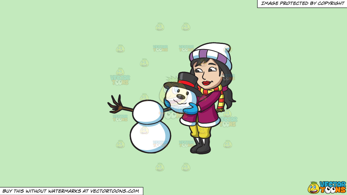 A Woman Placing The Head Of A Snowman On Top Of Two Snowballs On A Solid Tea Green C2eabd Background thumbnail